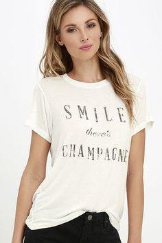"A glass of bubbly and the Daydreamer Smile There's Champagne Cream Tee are always a recipe for happiness! Soft and lightweight jersey knit tee has a crew neckline, short sleeves, and subtle high-low hem. ""Smile There's Champagne"" is spelled out on front in gold-flecked letters."
