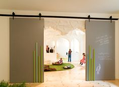Baukind - Kita Spreesprotten - the sliding partition door which doubles as a chalkboard for information for the parents and as a drawing area for the children. The exposed mechanism of the door feeds the natural curiosity of kids about the way things work.