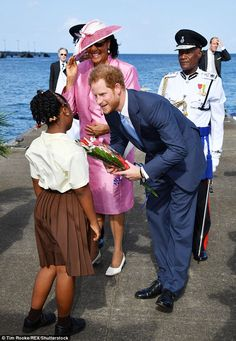 Prince charming: Harry chats to a little girl who presented him with a bunch of flowers...