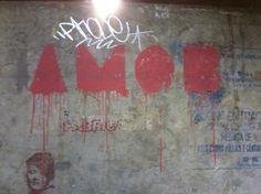 Detalhe da parede de um dos estúdios da FAU, nesse caso nota-se a sobreposição de várias mensagens, feitas em épocas diversas. Destaca-se a palavra amor no centro, tendo como suporte tinta vermelha aplicada sobre o concreto