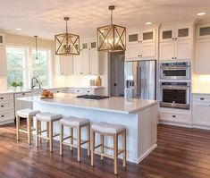 55 Gorgeous Kitchens with Stainless Steel Appliances (Photos) : White cottage kitchen with chandelier, marble breakfast island, bar stools, stainless steel appliances and hardwood flooring. Farmhouse Kitchen Interior, White Cottage Kitchens, Rustic Kitchen, Country Kitchen, Rustic Farmhouse, Kitchen Ideas, Kitchen Upgrades, Kitchen Modern, Farmhouse Ideas