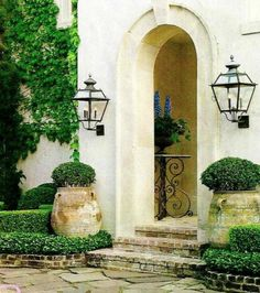 Interior designer Pam Pierce created a warm, welcoming entry at her home in Houston. A simple composition of boxwoods, French jardinières, a few gorgeous antique lanterns, and a French iron table.