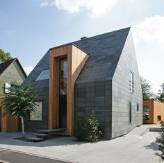 Contemporary black-clad house with monolithic door/window projection