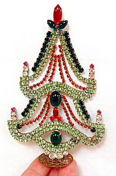 Vintage Czech Rhinestone Christmas Tree Village Standing Decoration (Image1)Czech glass self-standing Christmas Tree that is dripping with sparkling rhinestones. The rhinestone colors are mostly AB wash with ruby red garland and 'candle flames'plus gold-citrine topper. There are also tiny strands of pearl 'garland' under the red. 7 1/2 inch tall.