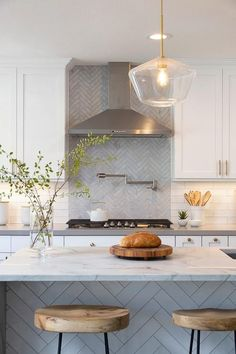 White shaker cabinets flank a stainless steel vent hood fixed to gray herringbone pattern tiles over a satin nickel swing arm pot filler fitted above a gas integrated cooktop.