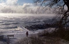 A woman walks along the beach while mist rises from a lake , January 13, 2015, in the east end of Toronto.