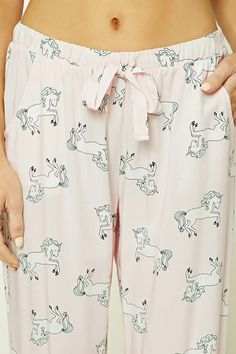 A pair of woven PJ pants featuring an allover unicorn print, two front slanted pockets, and an elasticized drawstring waist.