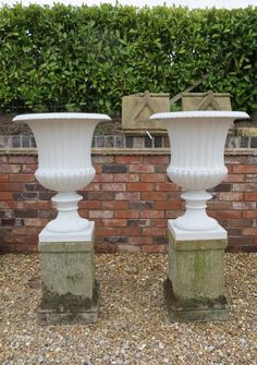 Pair of Cast Iron Planters On Reconstituted Stone Plinths. The planters have a circa of 1920.