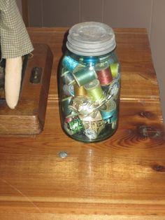 Old spools of thread in an old Mason jar.