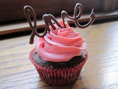 Chocolate strawberry cupcakes with piped chocolate toppers.