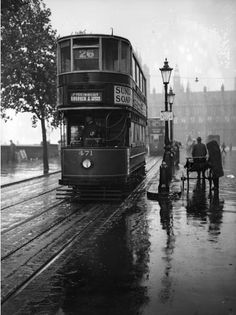 Commuters wait for a tram at Embankment, London, during a shower of rain. 1931