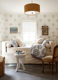 Cozy reading room features a white daybed dressed in soft blankets and pillows placed in front of a single window flanked by art work lining walls clad in white and blue print wallpaper.
