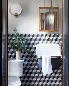 Graphic cement wall tile in a tumbling block pattern adds a bit of excitement to an otherwise quite traditional bathroom by Linden Harlow