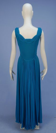 MADAME GRES PLEATED SILK JERSEY GOWN, 1970's. Sleeveless boned bodice having entwined knife pleating along back neckline, over the shoulder and down front to set-in waist having double self cord tie, full pleated skirt with knife pleats at center front and back, bodice lined in organdy, padded bust. Back
