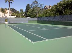 Traditional green tennis court with a lighter green wrap around