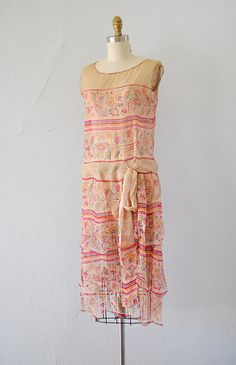 1920s whimsical and lovely flapper dress with pink stripes and floral print. This dress has tiered scalloped skirt, dropped waist, and ties at the hips. Sheer fabric.