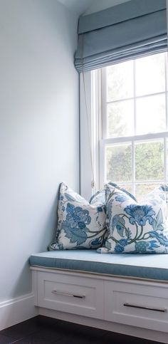 Bedroom reading nook is filled with built-in window seat with drawers topped with blue cushion with white piping as well as blue floral pillows under window dressed in blue roman shade.