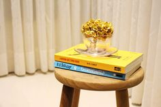 Coloque livros sobre um banquinho comum e ganhe uma mesinha de apoio! rsrsrs Banquinho comum, velhinho, em madeira crua.