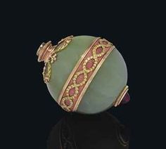 A GEM-SET BI-COLOR GOLD-MOUNTED BOWENITE AND GUILLOCHÉ ENAMEL BELL-PUSH  BY FABERGÉ, WORKMASTER'S MARK OF MICHAEL PERCHIN, ST PETERBURG, CIRCA 1890, SCRATCHED INVENTORY NUMBER 1582  Spherical bowenite body with band of pink guilloché enamel between reeded borders, with entwined laurel, upper mount surrounded by ribbon-tied swags, lower mount with a cabochon garnet push-piece. Purchased by Dowager Empress Maria Feodorovna (1847-1928) at Fabergé in St Petersburg on 14 April 1899 for 135 rubles.