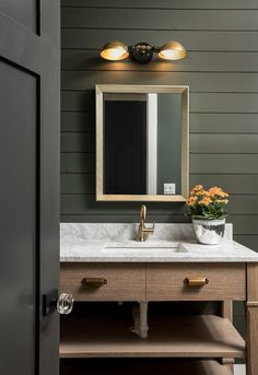 Modern rustic bathroom + black and white marble countertops + wooden bathroom cabinetry + dark green walls + dark wood doors + gold wall lighting | Picture Perfect House