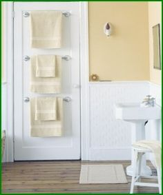 Towel racks behind bathroom door - great space saver for small bathroom. And perfect for guests. Everyone has their own towel and rack. GENIUS!