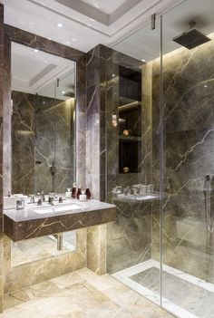 Private Apartment Belgravia | The girl's bathroom has Fior di Bosco flooring with a Calacatta marble border and underfloor heating, plus a step-free rain shower with recessed lighting and downlighting below the sink.