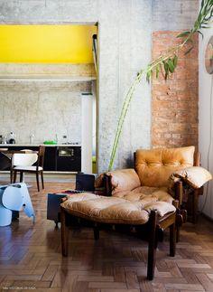 Vigas de concreto aparente, parede de tijolinho e poltrona mole na decoração da sala de estar de Carol Gay.