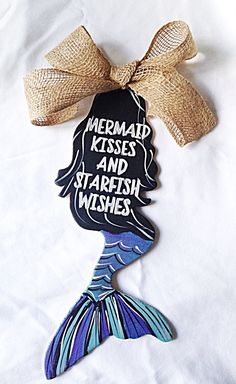 Mermaid Door Hanger with Burlap Bow. Perfect for a girls room as wall décor or for hanging on door. Hand Painted. Measures at 13 inches tall. Made of Wood