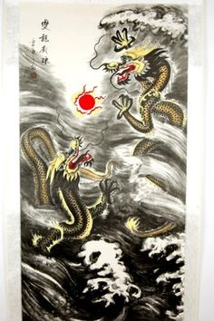"""In Feng Shui practice, double dragons are strong symbols of prosperity said to bring double good fortune. The calligraphy writing on this scroll translates to """"Two mighty dragons play with a wisdom pearl."""""""