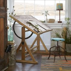 """WREN DRAFTING TABLE--Draw up your own plans for this beautiful natural pine and steel table. Use as a functional drafting table, a desk, or to display artwork. The table is edged at the bottom, its angle adjusts. Imported. 53""""W x 33""""D x 38""""H."""