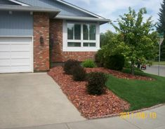 Driveway landscaping on a corner lot with a decorative rock to match the brickwork. Very simple and effective.