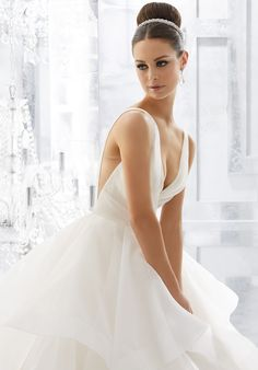 """Light and Airy, this Stunning Flounced Organza Ball Gown with Wide Horsehair Edging Features a Plunging V-Neck and Open V-Back. Illusion Insets Along Sides . Available in Three Lengths: 55"""", 58"""", 61"""". Colors Available: White, Ivory."""