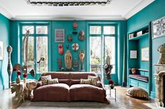 At fashion designer Stefano Pilati's Paris duplex, a collection of African masks is displayed in the living area, where the walls are covered in a vibrant teal.