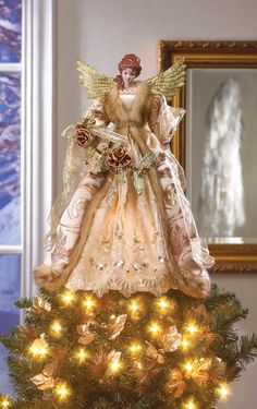 """#10015395 GOLDEN ANGEL TREE TOPPER This beautiful angel holiday tree topper has the look of a timeless treasure. Her glittering gold wings highlight her shimmering gown embellished with sequins, faux fur trim, and golden roses. Place her on top of your tree and enjoy her loving presence all holiday season long. Item Weight: 0.8 lb.  13"""" x 13"""" x 18"""" high.  Porcelain, plastic and polyester. $59.95"""