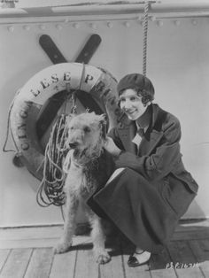 Claudette Colbert, French-born American stage and film actress, poses with a dog on board a boat, a lifebuoy behind her, c. 1930.