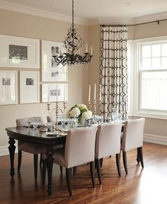 I like the way the curtains are hung in this dining room. The windows are similar to those in our dining room and I'd been wondering how I ought to do curtains in that room. I love the wall arrangement too, with different sized frames and matting for the black and white photos.