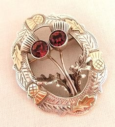 """Scottish silver, gold and amethyst thistle brooch, Edinburgh 1959,  2"""" tall and 1 1/2"""" across with a central section of 2 thistles with amethyst heads and with a ring of thistle patterns around the edge with the thistle heads and leaves in 9ct gold. This brooch was made in Scotland and hallmarked in Edinburgh."""