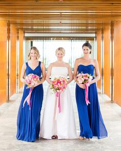 A Tropical, Colorful Wedding in Maui   Martha Stewart Weddings - Christen's bridesmaids wore long blue J.Crew dresses and carried pink bouquets. Together, the ladies were a perfect representation of the day's color palette.