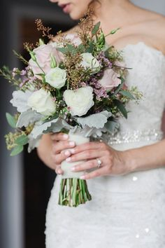 Bride's Hand Tied Bouquet Arranged With: White Ranunculus, White Lisianthus + Buds, Pastel Pink Roses, Light Lavender Waxflower, Green Seeded Eucalyptus & Dusty Miller