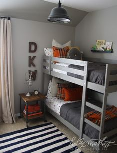 A cute gray and orange boys bedroom with gray bunk bed, small nightstand and schoolhouse-inspired metal light. By Holly Mathis Interiors