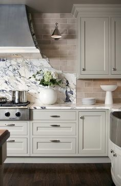 Greige cabinetry + marble. Wacky splashback love it..