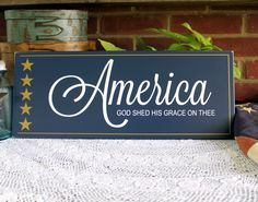 America God Shed His Grace on Thee       Handcrafted sign on a painted dark blue or burgundy worn finish with gold stars and measures 8 inches by 20 inches.   Decorative wall decor for Fourth of July or all year long.