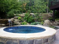 Custom built stone faced spa with limestone capped seating edge. Carved stone flowing waterfall which recycles the spa's water.