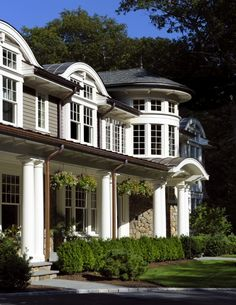 Great exterior with dark base and white trims and columns. It has a large front porch too. I love the white accents in the windows, and the rounded room near the right.