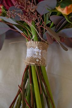 Simple--gather stalks with a strip of lace-embellished burlap. Secure with pearl pins.  | Andre Corvin Photography