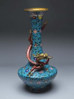 CHINESE DRAGON MOUNTED CLOISIONNIE ENAMEL VASEthe blue ground long necked bottle form vase with an entwined dragon. Height 21 in.