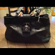 """Authentic Coach Handbag Authentic black leather handbag has silver hardware and a baby blue interior.  6"""" black leather handles and handbag has silver feet on the bottom.  Interior has two compartments - two zip pockets and two open pockets.  Very very light wear within the interior otherwise excellent condition. Coach Bags"""