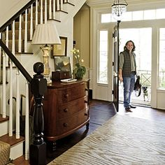 Homeowner and designer Jamie McPherson created an inviting entry in his central stair hall with a burled-mahogany, bow-front chest and faux- bois patterned rug.
