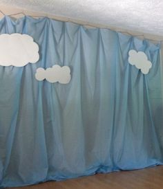 Katelyn's superhero party sky photo backdrop. Made from plastic table clothes and poster board clouds.