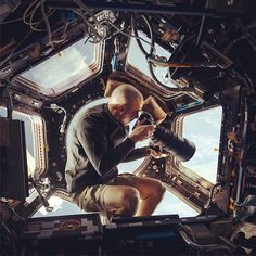Cassidy, an Expedition 36 flight engineer, is captured here using a 400mm lens to photograph Earth from the ISS. He's not photographing a supermodel in a bikini in Antarctica or snapping innocents in war-torn Sudan, he's taking a picture of Earth—which is 250 miles below him—from inside the Cupola observatory module on the ISS. Fantastic. [@Stephanie Anderson Goddard Space Flight Center, Image Credit: NASA]